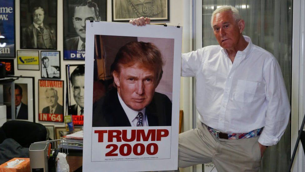 Roger Stone holding a Trump 2000 campaign poster