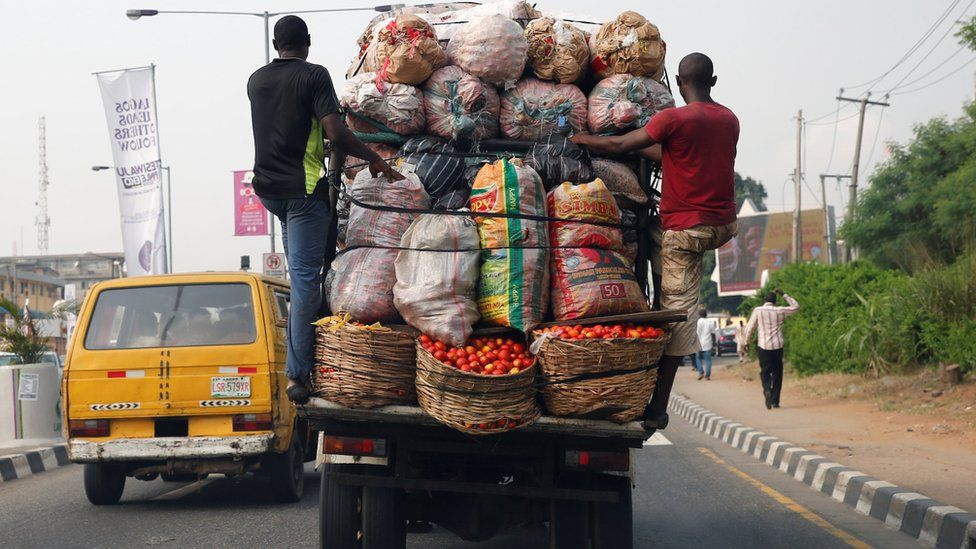 Men hang at the back of a truck loaded with farm produce along a road in Nigeria's commercial capital Lagos