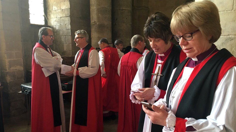 Bishop holding smartphones