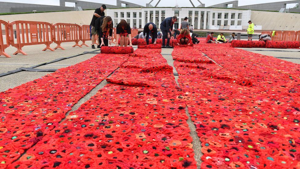 European Union ambassadors help with the installation of 270,000 poppies, ahead of Remembrance Day commemorations, outside Parliament House in Canberra, Australian Capital Territory, Australia on Wednesday