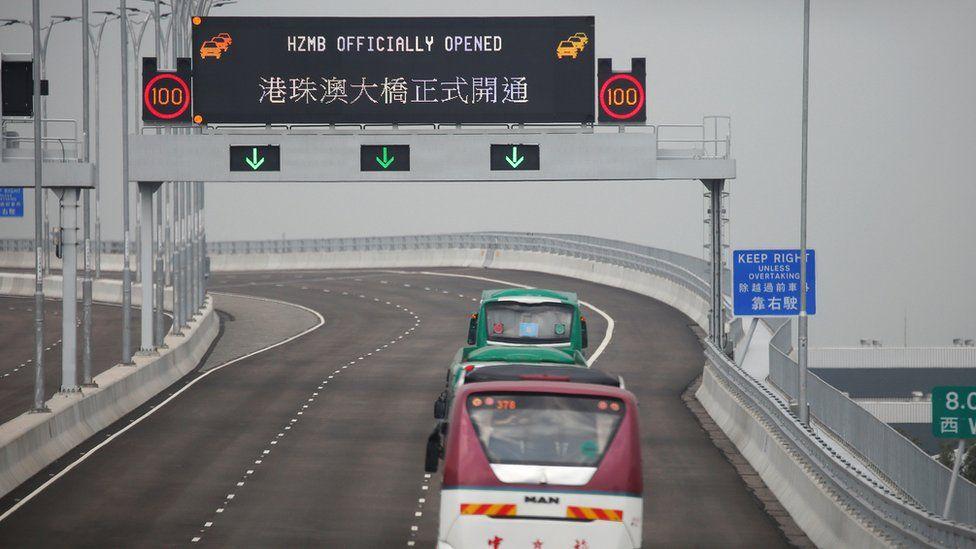 Buses drive past a sign on the Hong Kong-Zhuhai-Macau Bridge offshore in Hong Kong