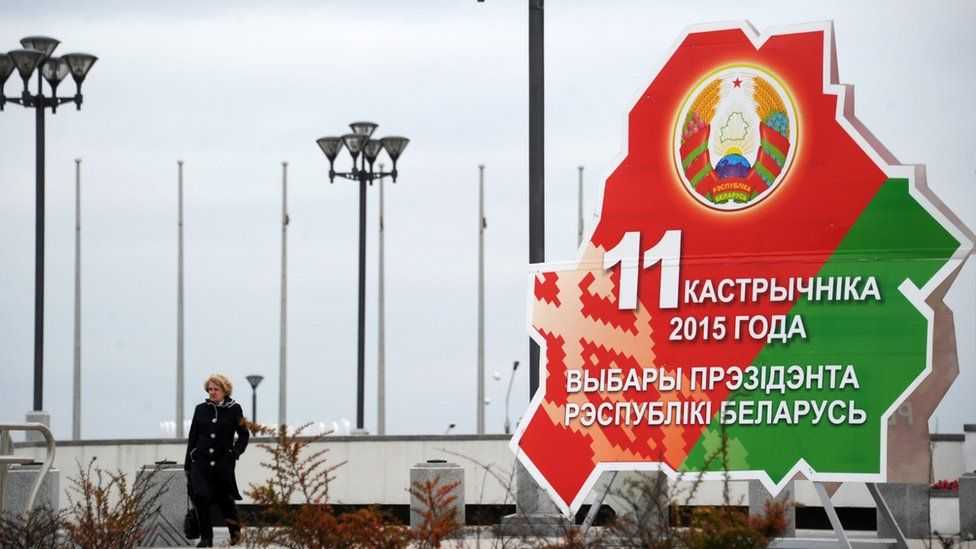 A woman walks past the Belarussian presidential election banner