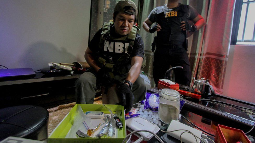 National Bureau of Investigation (NBI) operatives inspect the confiscated materials prohibited inside the New Bilibid Prison in Muntinlupa, south of Manila on December 16, 2014