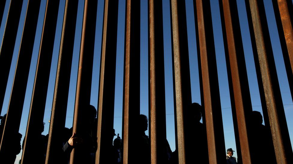 People stand at wall at the southern border