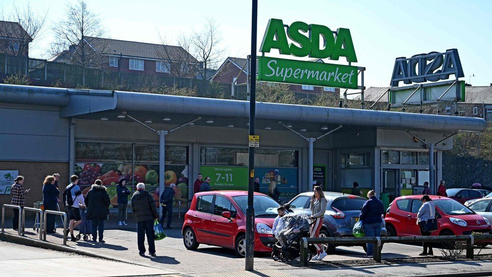 Shoppers queue outside a supermarket