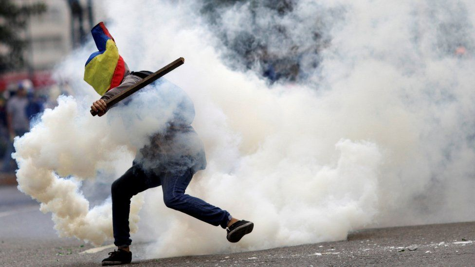 A demonstrator clashes with riot security forces during a rally against the Venezuelan government in July 2017
