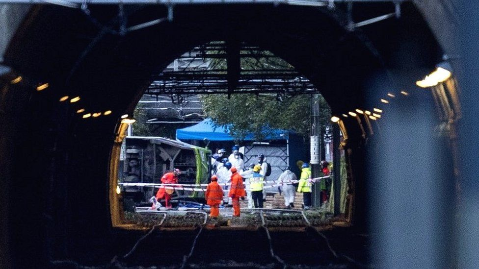 Emergency workers carry a stretcher away from an overturned tram