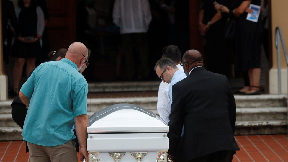 A coffin is carried into the church