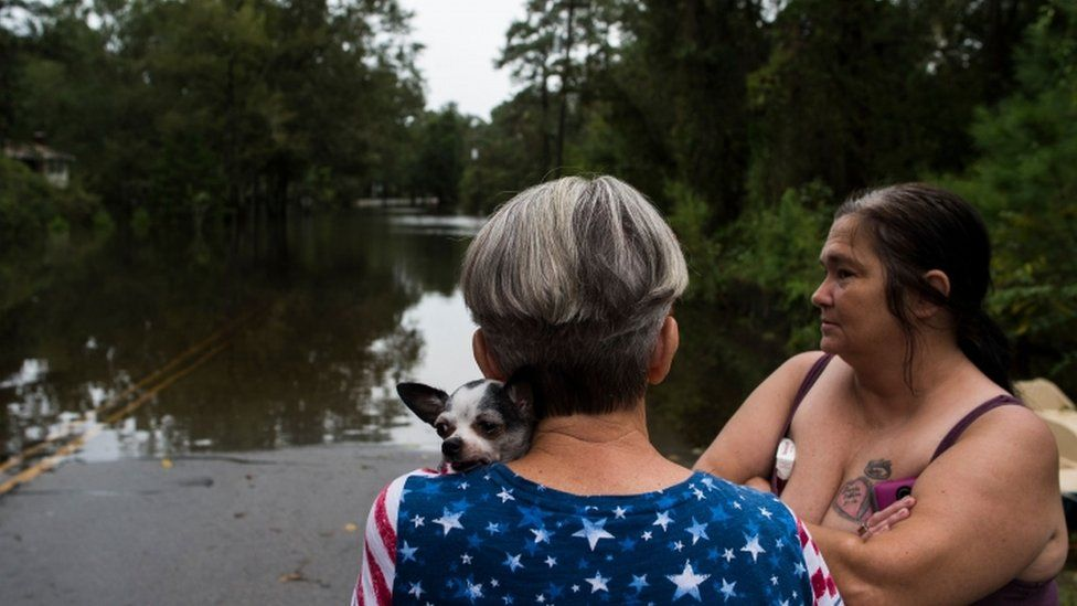 Residents look at a street in a neighbourhood flooded from heavy rains after Storm Florence