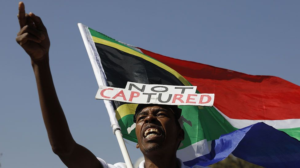 A supporter of the Organisation Undoing Tax Abuse (Outa) holds a South African flag while picketing outside Raymond Zondos judicial commission of inquiry into state capture at Parktown on August 20, 2018 in Johannesburg, South Africa.