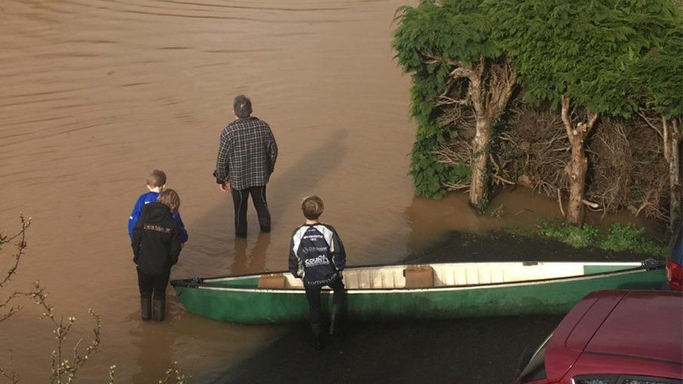 A family in Monmouthshire prepare a canoe on their driveway