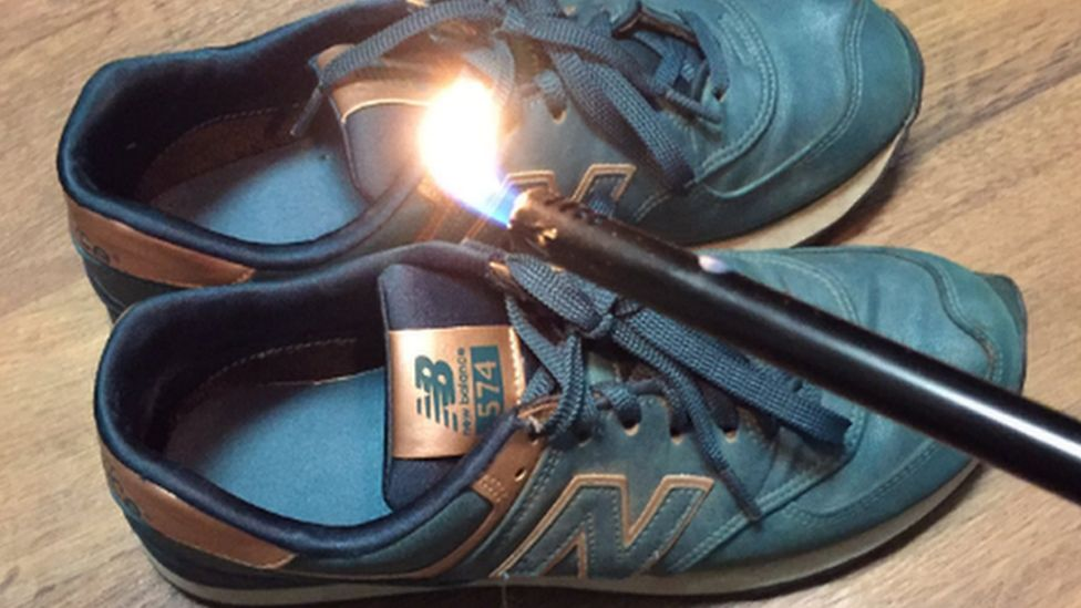 This is a photo of some New Balance trainers being set alight.