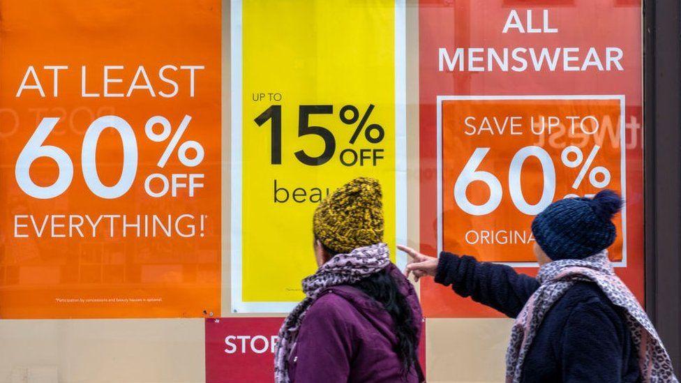 Shoppers outside a Debenhams store