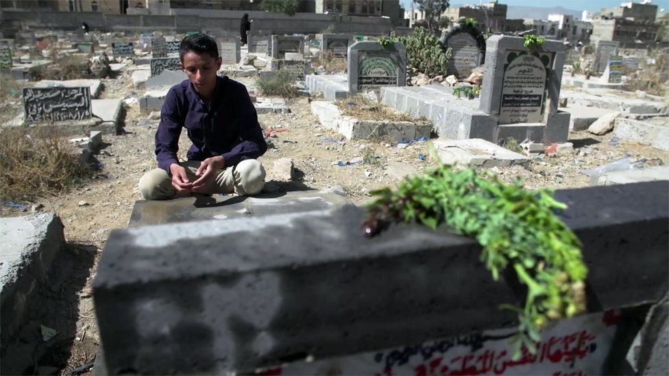 Awab sits beside his father's grave at a cemetery in Sanaa, Yemen