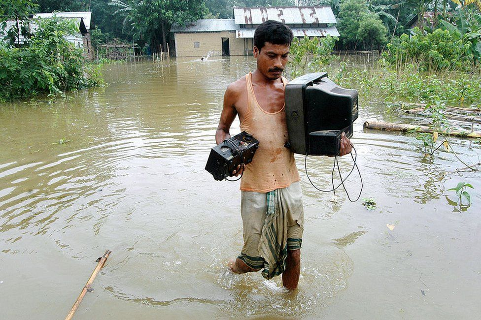 An Indian man carries a television set through flood water in the flood-affected village of Nellie, in the Morigoan district, some 75 km from Guwahati, the capital city of India?s northeastern state of Assam, 10 September 2007.