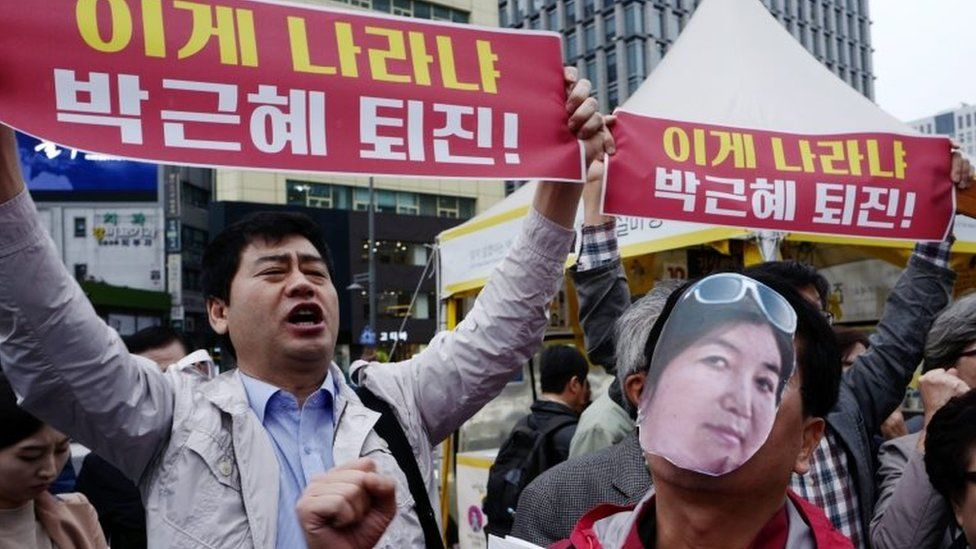 """A protester (right) wears a cut-out photograph of Choi Soon-sil, while another demonstrator holds a banner reading: """"President Park Geun-hye's resignation"""" in Seoul on 27 October 2016"""