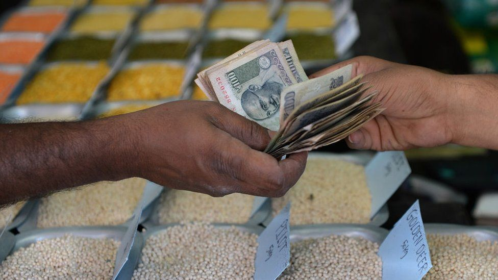 An Indian customer hands over cash to a food grain merchant at a wholesale trading shop in Bangalore