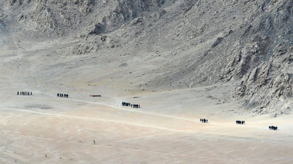 Indian soldiers walk at the foothills of a mountain range near Leh, the joint capital of the union territory of Ladakh, on June 25, 2020.