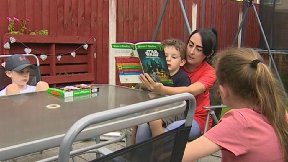 Stephanie Barnett reads to her children in her garden in Connah's Quay, Flintshire, during coronavirus lockdown