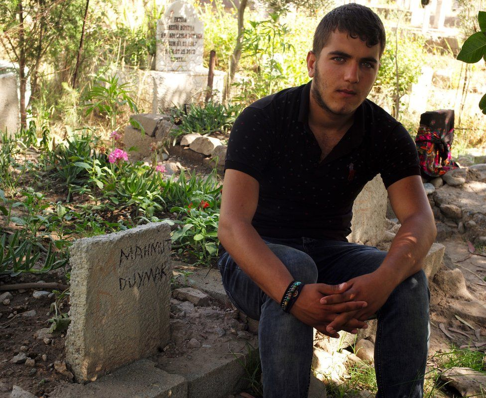 Firat Duymak, 18, next to his father's grave in Cizre, Turkey - May 2016