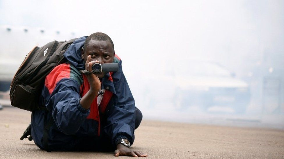 A Ugandan journalist uses his camera after riot policemen fired tear gas to disperse activists led by musician turned politician, Robert Kyagulanyi, during a demonstrating against new taxes including a levy on access to social media platforms in Kampala, Uganda July 11, 2018