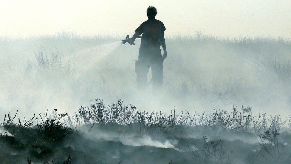A firefighter tackles wildfires in Lancashire