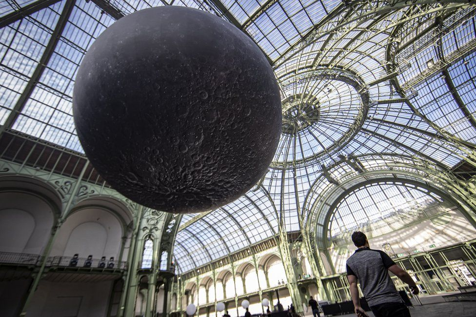 "A replica of the moon hangs from the glass ceiling of the Grand Palais ahead of the ""Mooon Party"" celebrating the 50th anniversary of the moon landing, in Paris, France"