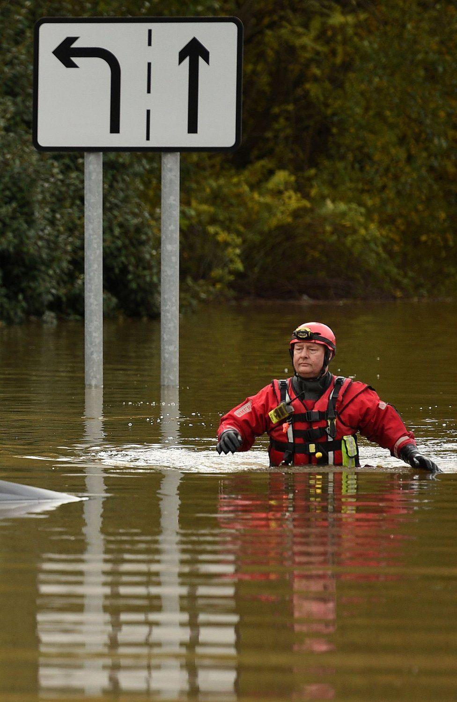 Një anëtar i shërbimit të Zjarrit dhe Shpëtimit përhapet përmes ujit të përmbytjes