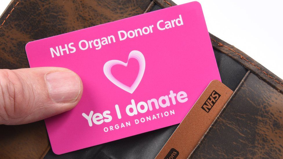 NHS organ donor being held in front of a wallet