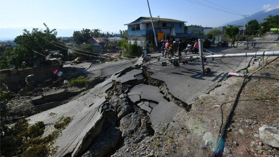 Workers assess a badly cracked road in Palu