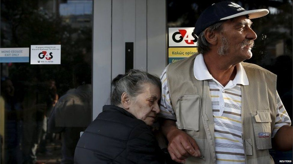 Vallia (L), a 75-year-old pensioner from Athens, holds onto the door of a branch of the National Bank of Greece hoping to get her pension, next to other pensioners in Athens, Greece June 29, 2015.