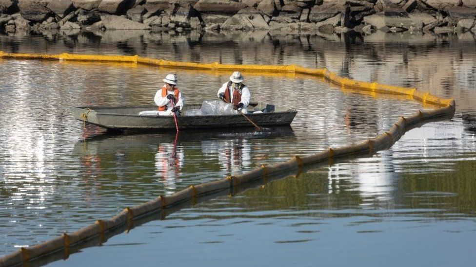 Crews work to prevent further contamination after an oil spill