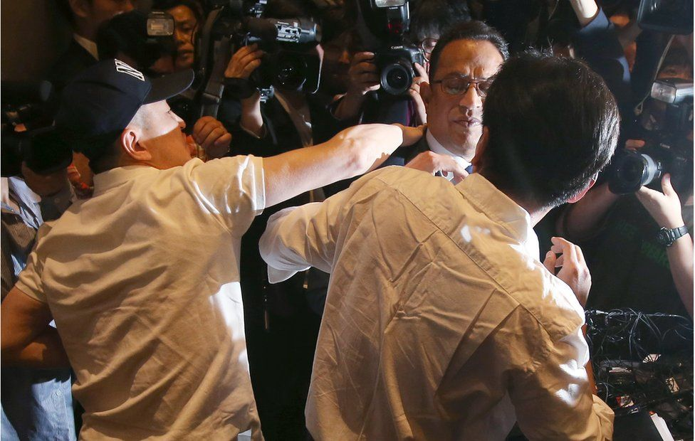 Atar Safdar (C), the head of Oxy Reckitt Benckiser Korea, is surrounded by the aggrieved relatives of victims as he bows during a press conference at a hotel in Seoul on 2 May 2016.