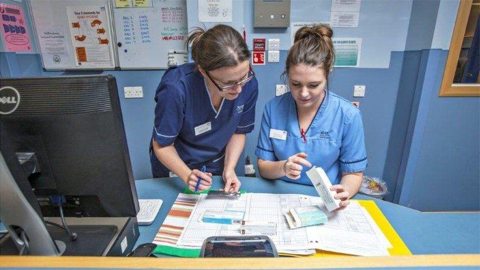 Nurses talking at a desk