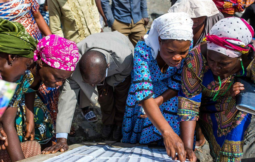 Voters look for their names on the electoral roll outside the Kibancha polling station in Sake, North Kivu, on December 30, 2018.