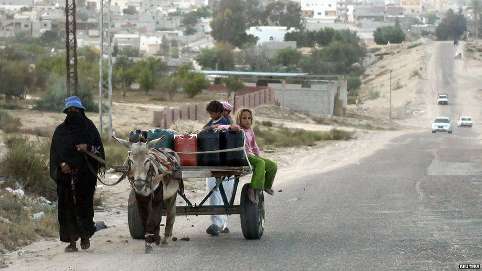 A family uses a donkey to transport water on a road in Sheikh Zuweid, Egypt (24 May 2015)