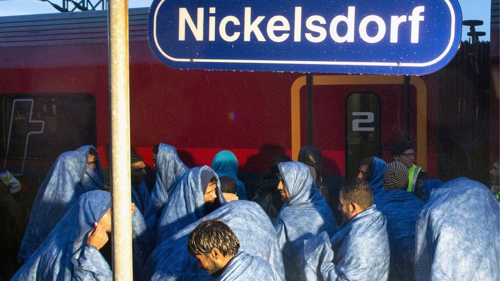 Migrants board a train in the village of Nickelsdorf in early hours on September 5, 2015