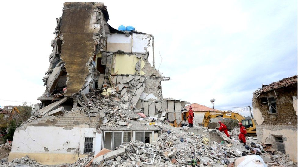 Italian rescuers search for survivors through the rubble of a collapsed building in Thumane, 27 November 2019