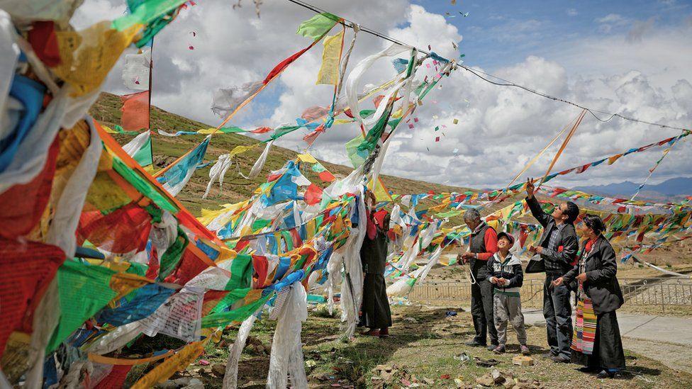 Buddhist believers hang prayer flags at a mountain pass