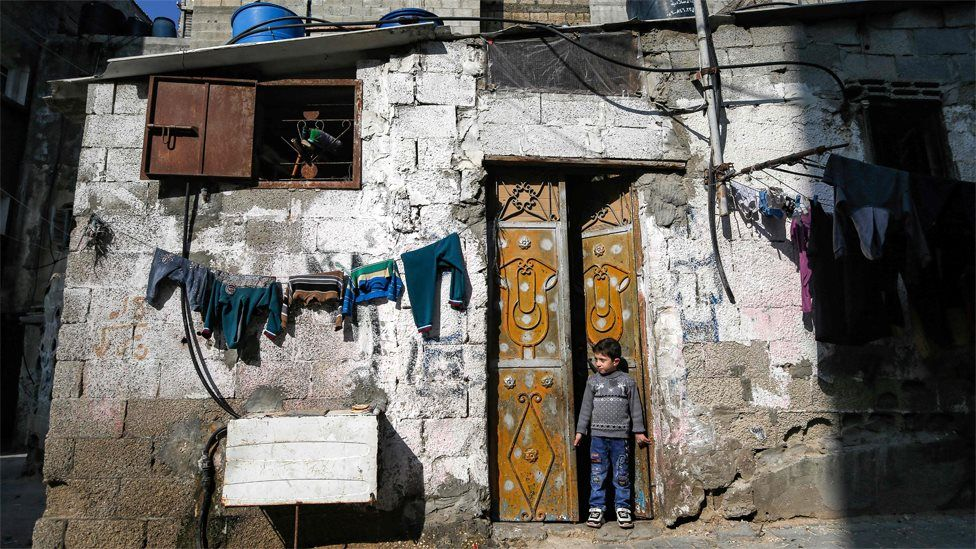 A Palestinian boy stands in the door of a house at the al-Shati refugee camp in Gaza City (28 January 2020)