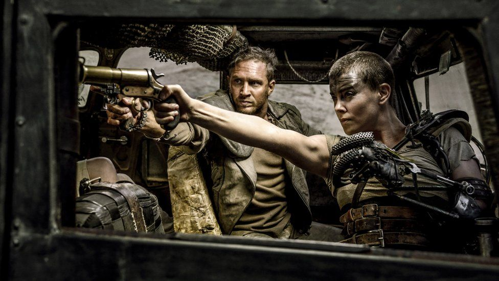 Tom Hardy, center, as Max Rockatansky and Charlize Theron, right, as Imperator Furiosa