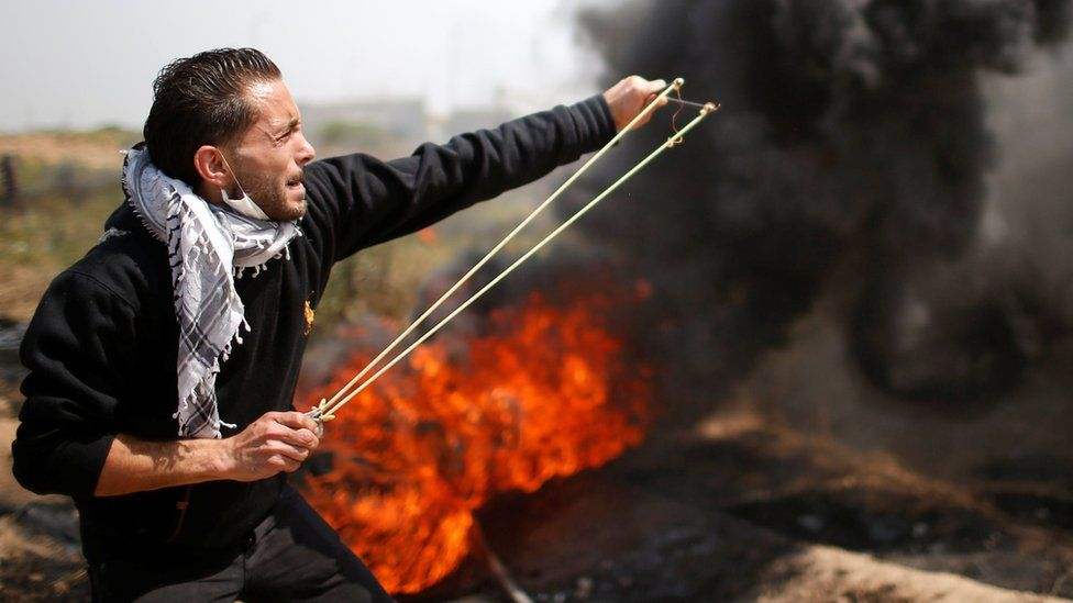 Palestinian man uses a catapult to fire stones during east of Gaza City on 6 April 2018