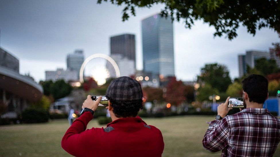 Two people are shown taking photos of Atlanta's skyline.