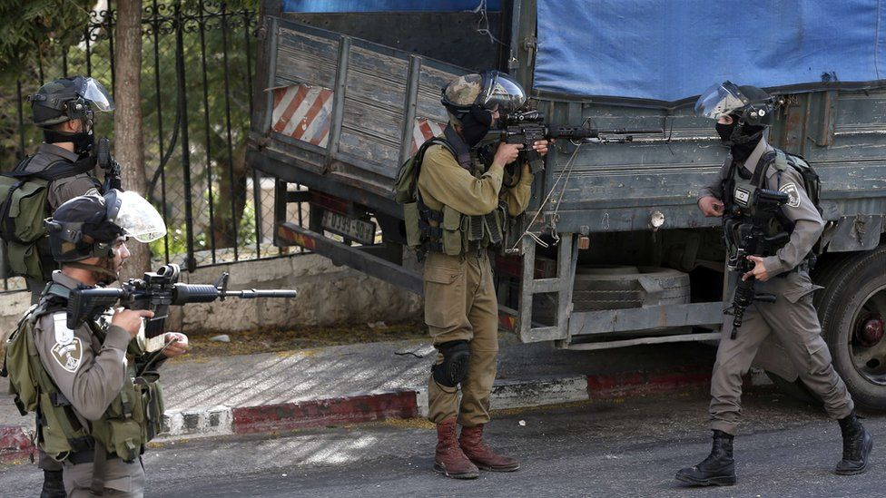 An Israeli soldier at Palestinian demonstrators during clashes in the West Bank town of Bethlehem (5 October 2015)