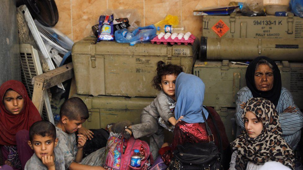 Displaced Iraqi civilians rest at an Iraqi security forces position in the Old City of Mosul (29 June 2017)