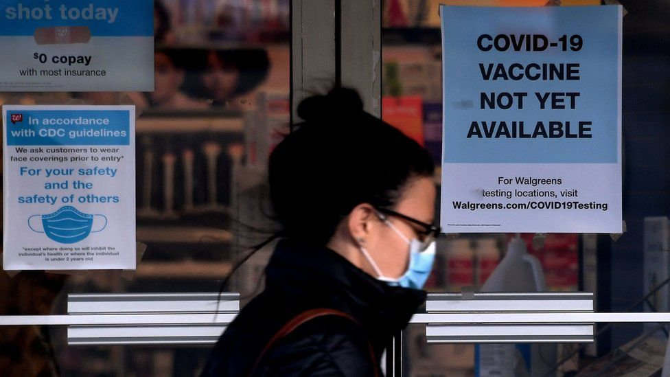 """A woman walks past a """"Covid-19 vaccine not yet available"""" sign outside a store in Arlington, Virginia on December 1, 2020"""