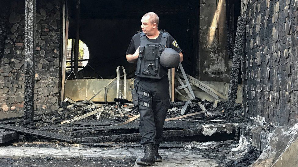 A police officer inspects the site of a burnt house reportedly owned by former Governor of the Ukrainian Central Bank Valeria Gontareva, in Kiev