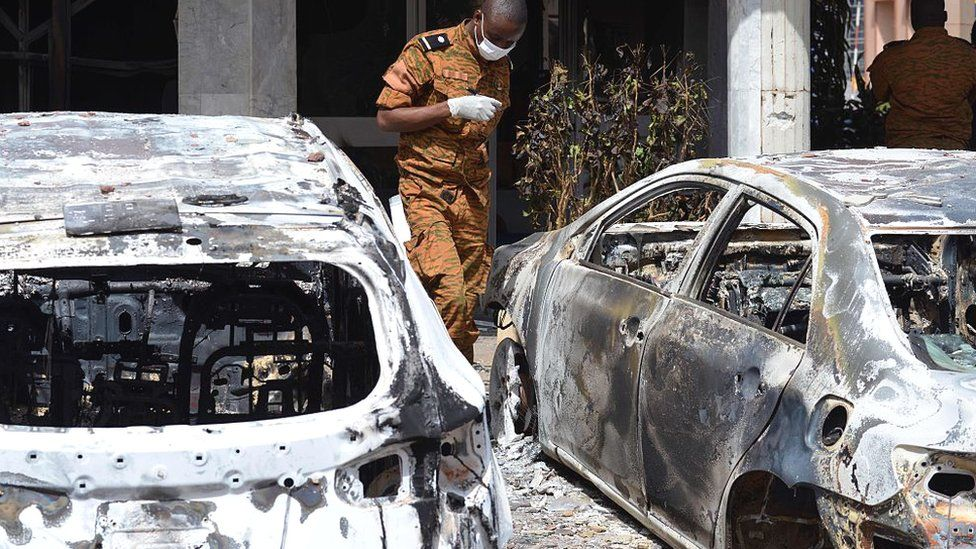 A Burkinabe investigator walks next to burnt cars in front of the Splendid hotel, on 17 January 2016 in Ouagadougou, following a jihadist attack