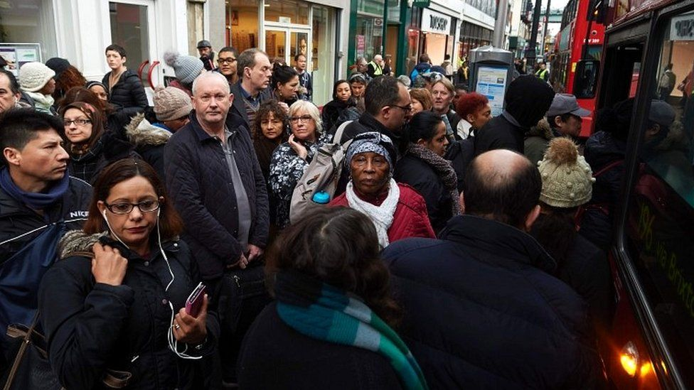Commuters wait to board buses at bus stops in Brixton