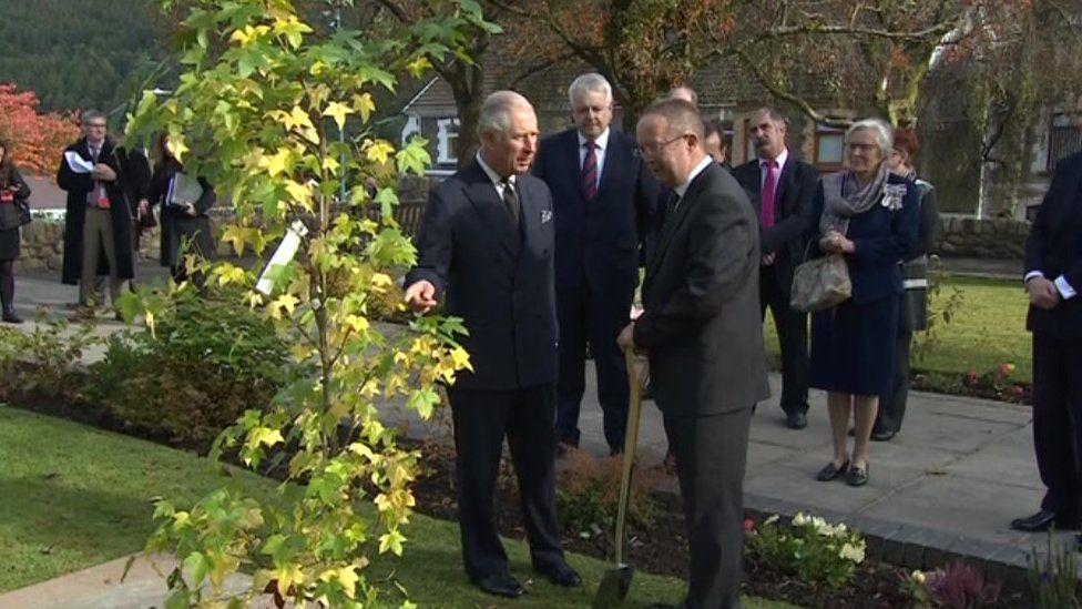 Welsh Secretary Alun Cairns and First Minister Carwyn Jones watch as Prince Charles plants a tree at the Aberfan memorial garden